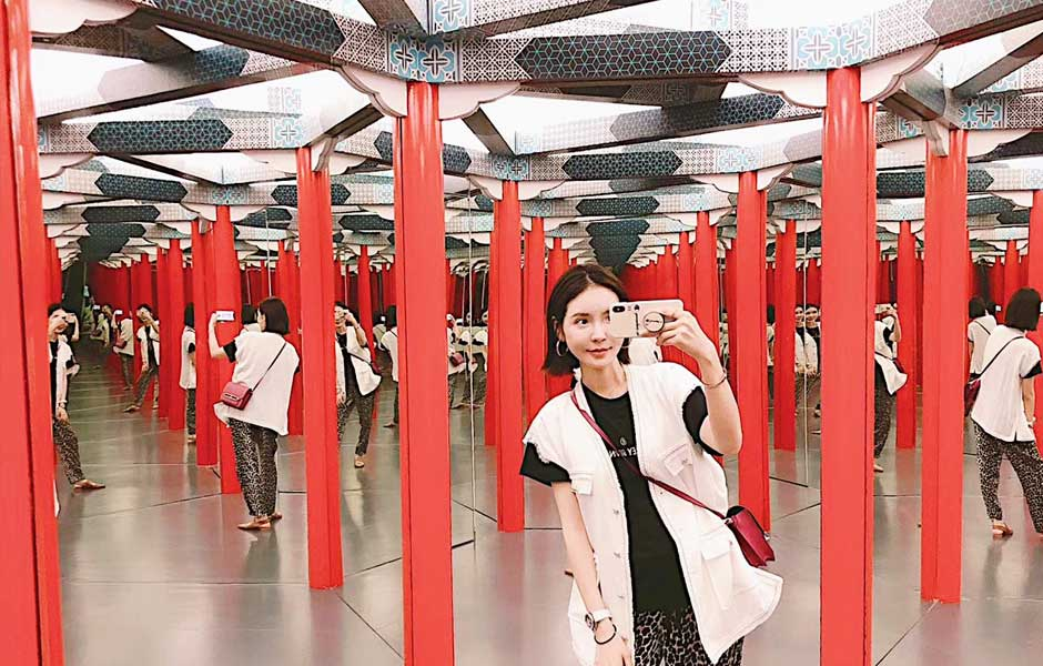 woman taking picture in an infinity room