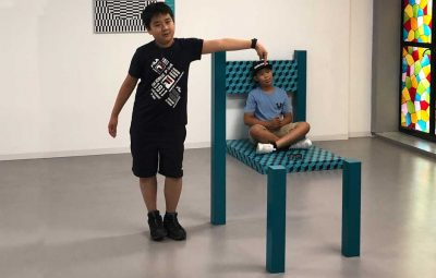 two boys taking photo with chair illusion