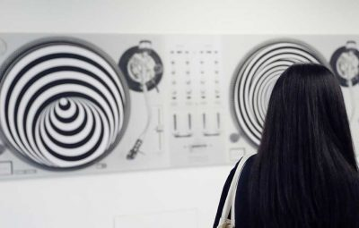woman looking at turntables exhibit